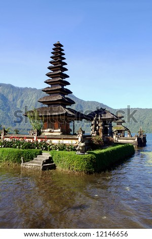 Vertical view of picturesque Balinese temple on lake in extinct volcano crater - stock photo