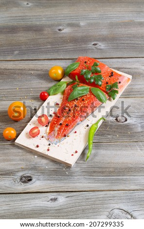 Vertical view of raw red salmon, skin side down, on maple wood grilling plank with seasoning and other herbs  - stock photo