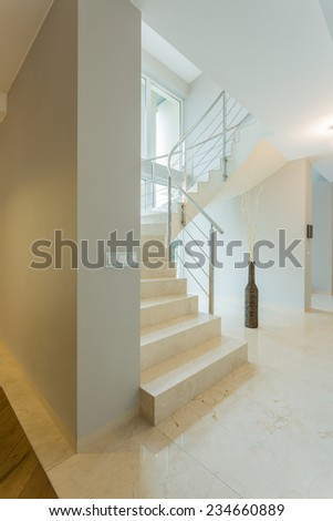 Vertical view of white interior with marble stairway - stock photo