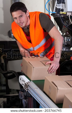 Vertical view of worker next to production line - stock photo