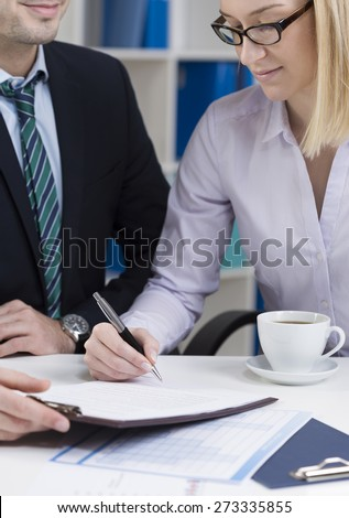 Vertical view of young businesswoman signing contract - stock photo