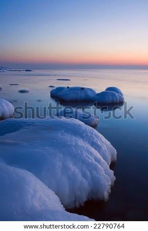 Vertical view on the winter sea and frozen stone