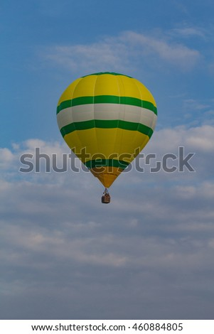 Vertical Yellow Green and White Striped Hot Air Balloon Ascending