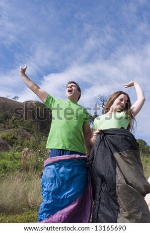 Vertically framed outdoor shot, looking up towards the sky, of a young attractive couple standing in their sleeping bags yawning as they awake from their slumber. - stock photo