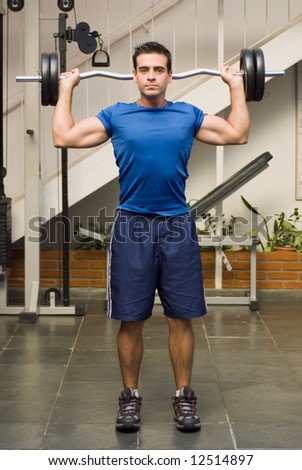 Vertically framed shot of an athletic, handsome male with a barbell behind his back in a gym - stock photo