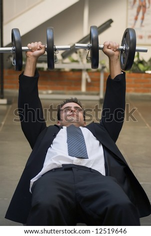 Vertically framed shot of an athletic, young businessman bench pressing weights in a gym - stock photo