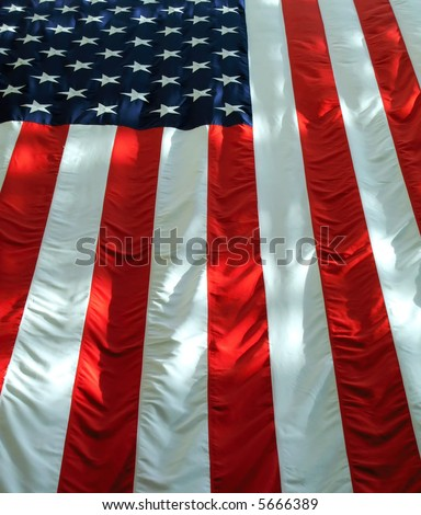 Vertically hung American flag with light and shadows. - stock photo