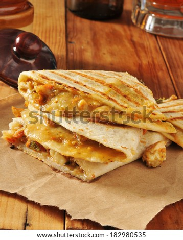 Verticle shot of grilled chicken quesadillas with beer - stock photo