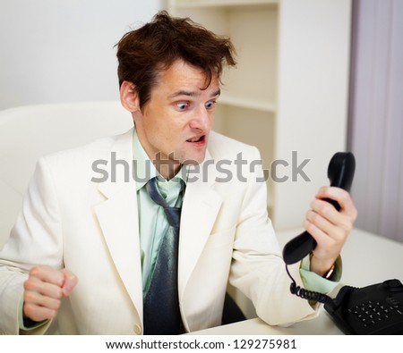 Very angry business man in white office with telephone handset