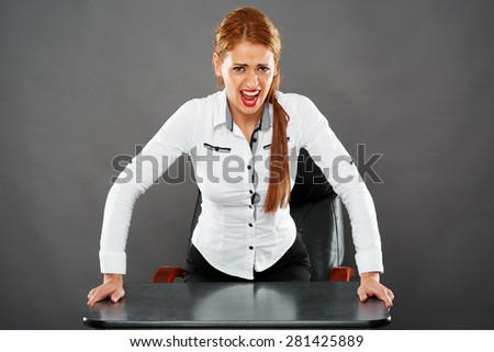 Very angry businesswoman clinging to her desk while yelling at the camera - stock photo