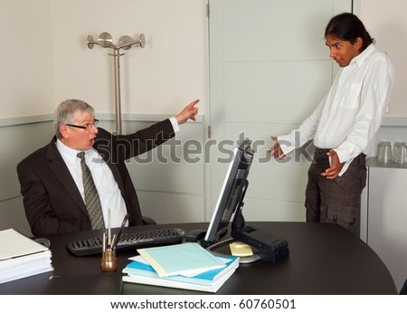 Very angry director firing one of his young employees - stock photo