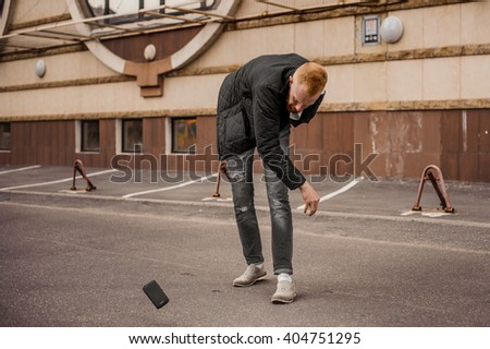 very angry man is throwing away his mobile phone - stock photo