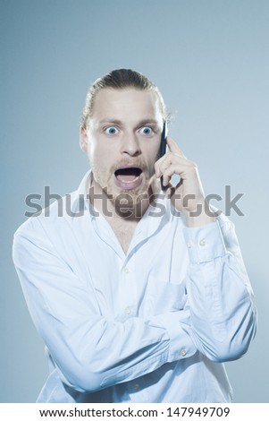 Very angry man on telephone  - stock photo