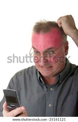 Very angry man with a exaggerated facial expression looking at a cellphone and turning red in the face. - stock photo
