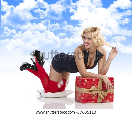 very attractive and sexy blond pin up with red christmas stocking and a big present box laying on the floor with sexy pose against white background