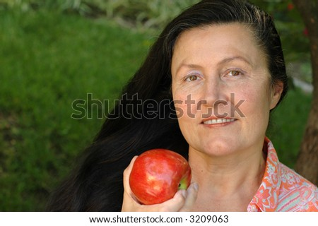 Very attractive older woman enjoying an apple in her garden.  Healthy senior lifestyle concept. - stock photo