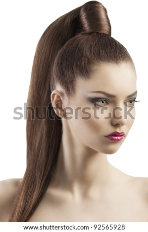 very attractive young brunette with long hair and tail and creative hair style looking luxury and proud, she is turned of three quarters and looks down at left with searius expression