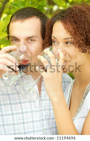Very attractive young couple enjoying a glass of wine outdoors - stock photo