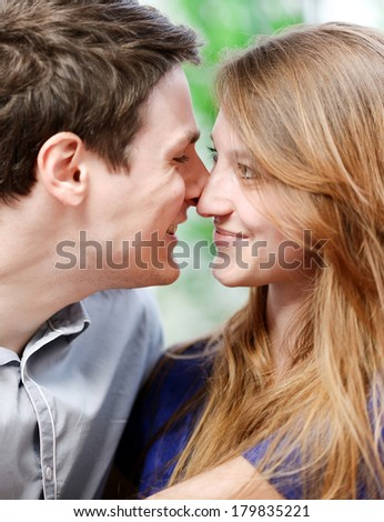 Very attractive young couple flirting on a sofa in living-room - stock photo