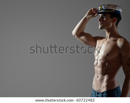 very attractive young male model top naked with a sailor cap, great body - studio shoot - copy space - stock photo