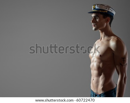 very attractive young man model top naked with a sailor cap, great body - studio shoot - copy space - stock photo