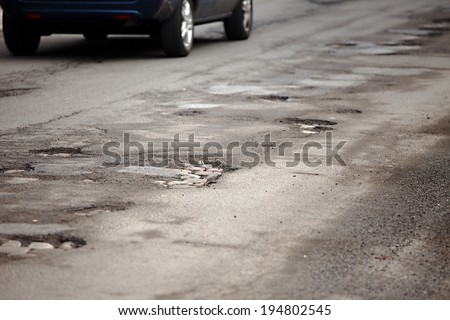 Very bad quality road with potholes - stock photo
