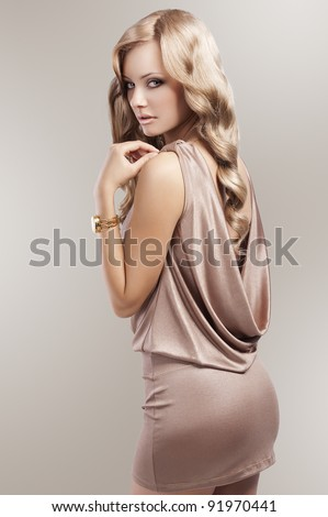 very beautiful and attractive young blond woman in elegant silk dress and with old fashion hair style and golden clock - stock photo