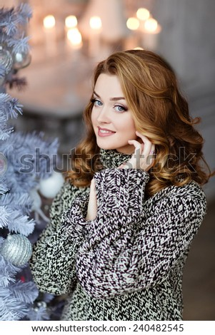 Very beautiful and sensual blonde girl in a knitted sweater smiles on the background of the Christmas tree - stock photo