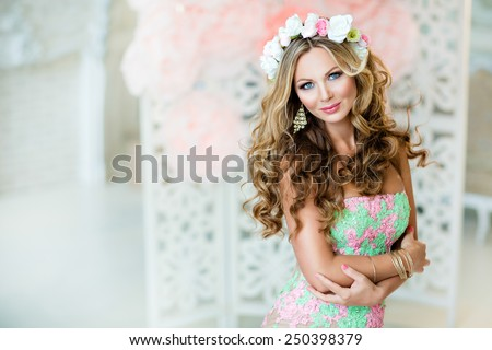 Very beautiful and sensual blonde girl in a lace dress with a wreath of flowers on his head, close up - stock photo