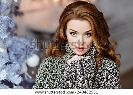 Very beautiful and sensual blonde girl with blue eyes in knitted grey sweater on the background of the Christmas tree, close up - stock photo