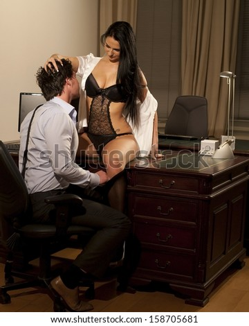 Very beautiful and sexy woman in lingerie is sitting on a desk and  is working late with her  manager at the office - stock photo