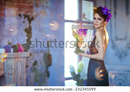 very beautiful brunette woman with flowers in her hair holds the cage in his hands on a blue background - stock photo