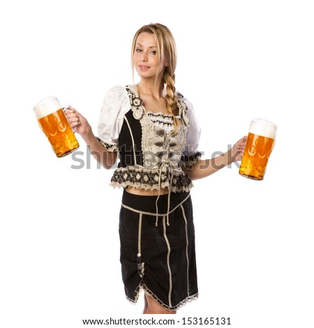 very beautiful caucasian white woman in traditional tiroler costume or outfit is holding a big glass of beer in her hands - stock photo
