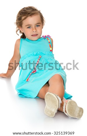 Very beautiful cute little girl dressed in a blue dress sitting on the floor legs-Isolated on white background