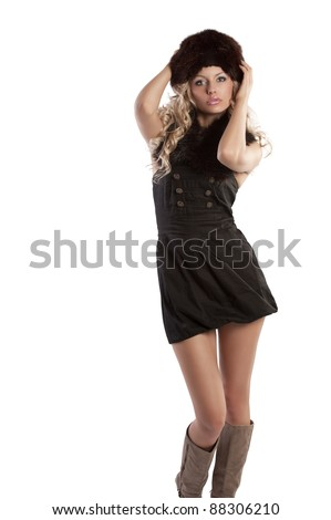 very beautiful fashion woman wearing an elegant black dress with boot and winter fur hat with stole - stock photo