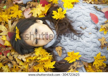 Very beautiful girl in gold leaves