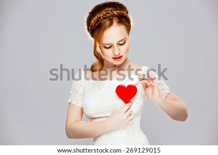 Very beautiful girl with red hair, in a braid holding a red Lollipop in the shape of a heart, beauty in the Studio on a white background - stock photo