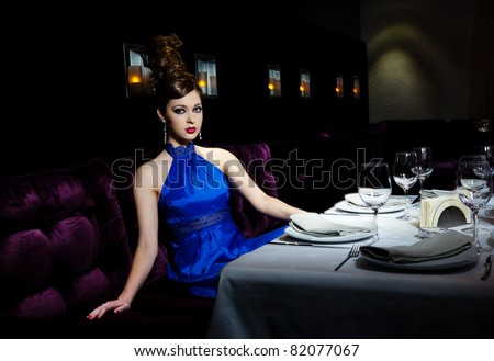 Very beautiful glamour girl in a dark blue dress sits at restaurant at a table - stock photo