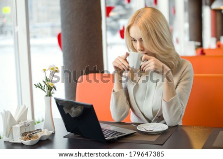 Very beautiful, happy,  young businesswoman, sit in  Cafe  with laptop netbook and drink coffee, horizontal portrait - stock photo