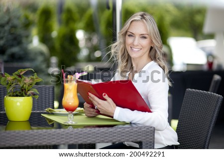 Very beautiful, happy, young woman, sit in Cafe and drink cocktail, horizontal portrait - stock photo