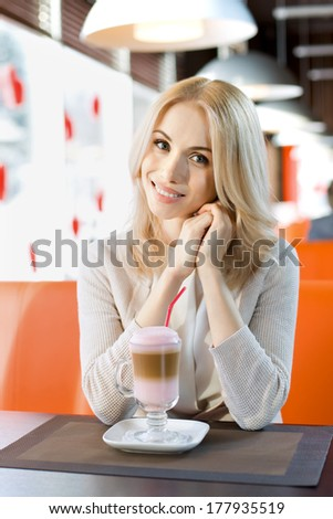 Very beautiful, happy,  young woman, sit in  Cafe and drink coffee- cocktail, vertical portrait