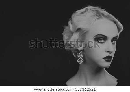 Very beautiful image of the model in vintage dress on a dark background. Portrait black and white photo blonde lady in the form of 20th years. Stylish jewelry. Professional makeup.
