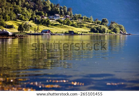 Very beautiful landscape view of the cozy little houses on the hill and the beautiful reflections in the water of the fjord in Norway in the summer - stock photo