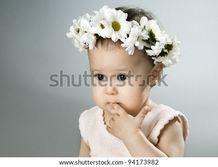 very beautiful  little kid with diadem of flowers,  sorrowful ,  closeup face - stock photo