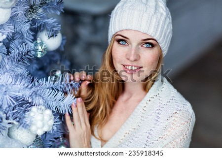 Very beautiful red-haired girl with blue eyes in a white hat about silver Christmas tree, close up