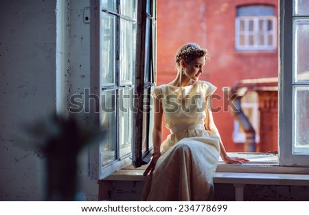 very beautiful sensual girl in a white dress looking out of the window - stock photo