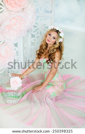 Very beautiful sensual girl with curly blond hair and a wreath of delicate spring flowers, sitting on the background of large pink flowers and white cells - stock photo