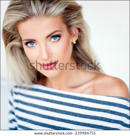 very beautiful, sensual sexy blonde girl with blue eyes in a striped dress, close up - stock photo