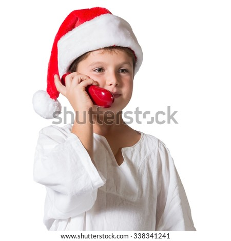 Very beautiful seven year old boy in a red cap. He is talking on the red phone - stock photo
