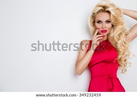 Very beautiful sexy blond-haired woman girl in a sexy short red dress crystals with long legs standing on a white background holding hands above his head - stock photo
